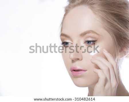 Woman put cream on a face - stock photo