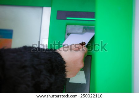 Woman put her credit card at the ATM  - stock photo