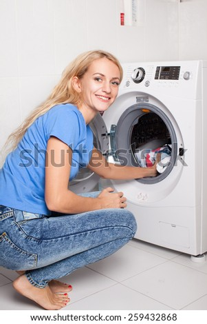 Woman puts clothes in the washing machine at home - stock photo
