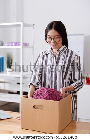 Woman putting a ball of threads back into the box