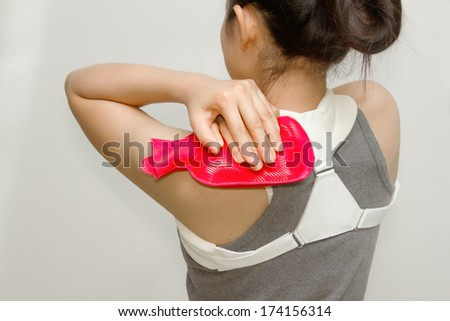 woman putting a hot pack on her shoulder pain - stock photo