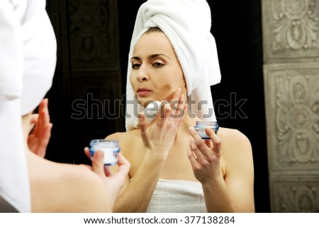 Woman putting anti-aging cream on her face. - stock photo