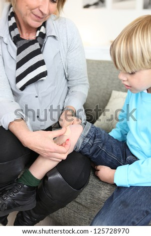 woman putting bandage to little boy - stock photo
