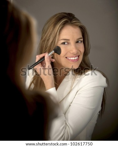 Woman putting blush on her cheeks - make up concepts - stock photo