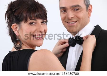 Woman putting bow tie to man - stock photo