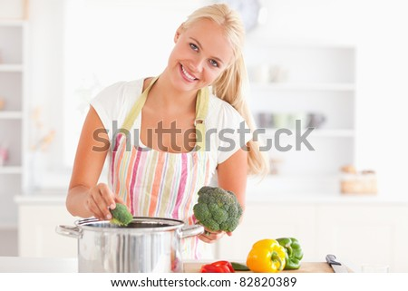 Woman putting cabbage on water while wearing an apron - stock photo
