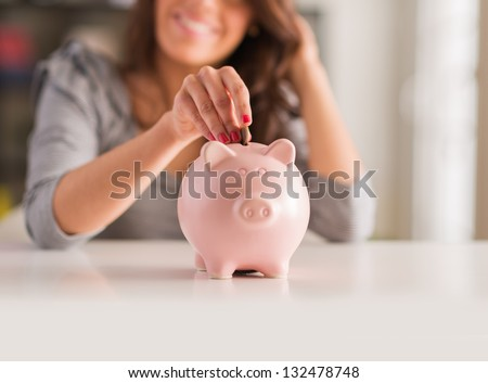 Woman Putting Coin In Piggy Bank, Indoors - stock photo