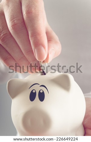 Woman putting coin in piggy coin bank, selective focus with shallow depth of field