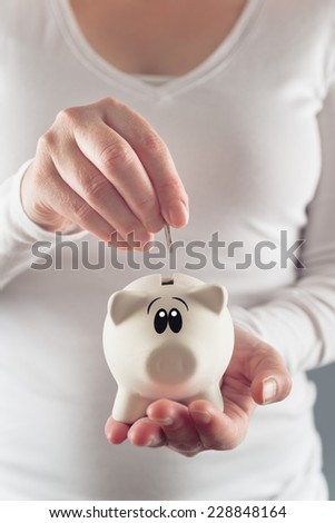 Woman putting coin in piggy coin bank, selective focus with shallow depth of field - stock photo