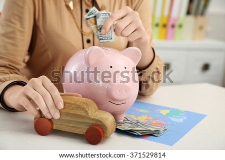 Woman putting dollar banknotes into piggy bank. Savings money for travel concept - stock photo