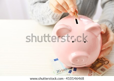 Woman putting euro coin into a piggy bank on the table. Financial savings concept