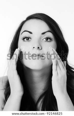 woman putting face cream on her face. - stock photo