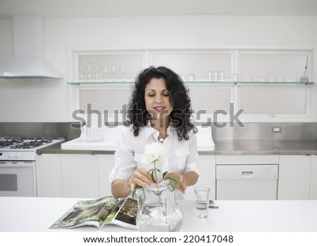 Woman putting flower in vase in kitchen - stock photo