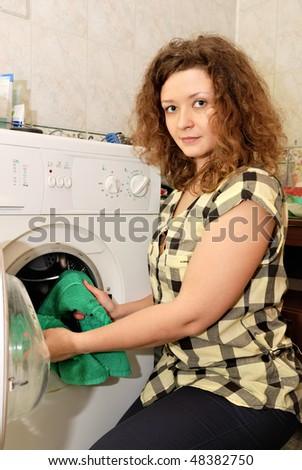 woman putting linen into washing machine - stock photo