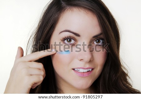woman putting lines under her eyes as if ready for war like - stock photo