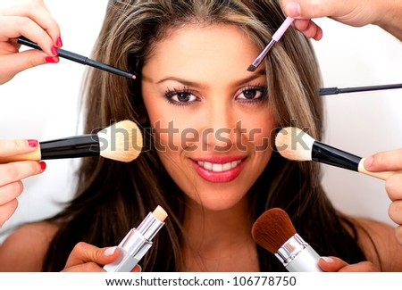Woman putting makeup on by professional styling people - stock photo