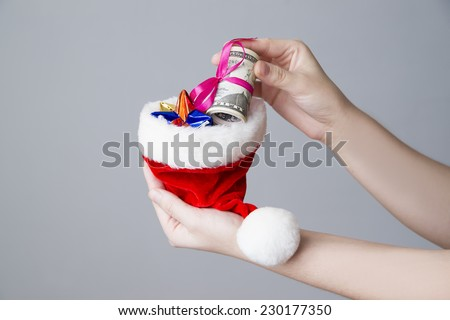 Woman putting money in a Santa hat on gray background. Christmas. - stock photo
