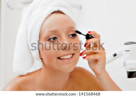Woman Putting on Make up - stock photo