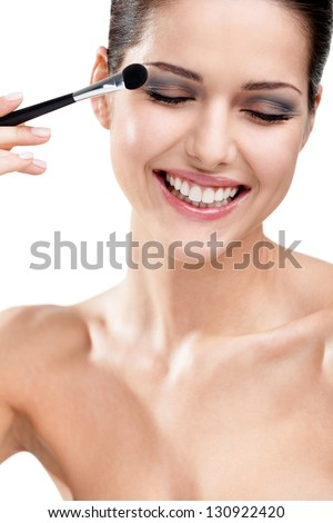 Woman putting on make-up with brush, isolated on white. Beauty procedures - stock photo