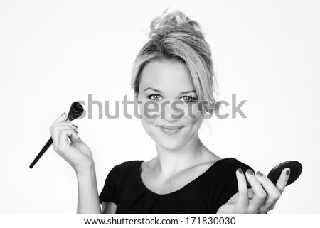 woman putting on makeup shot in the studio against a white background