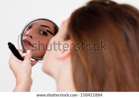 Woman putting on mascara in a mirror - stock photo