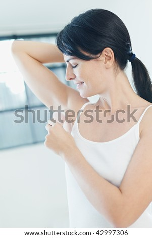 woman putting on stick deodorant and smiling. Side view - stock photo