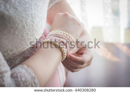 Woman putting on white and pink pearl beaded bracelets with focus on hands and wrist closeup in pink and white lace wedding dress as bridal preparation getting ready photos