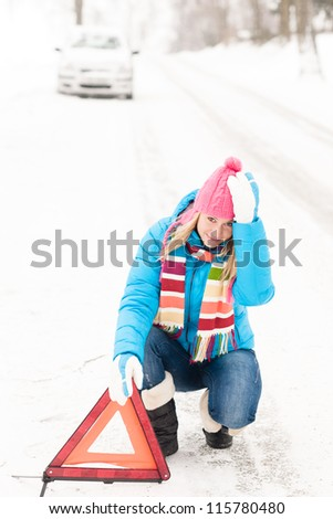 Woman putting reflector triangle car breakdown winter snow sign - stock photo