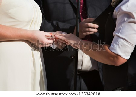 Woman putting ring on finger of partner in civil union - stock photo