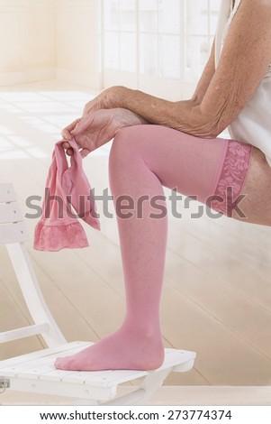 Woman putting thrombosis stockings on - stock photo
