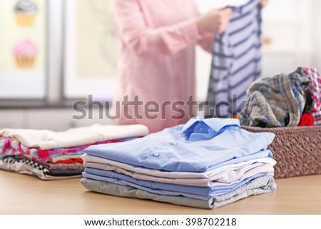 Woman putting together clothes in the room - stock photo