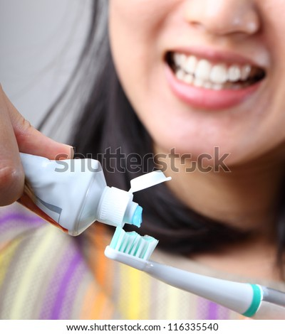 Woman putting tooth paste on her toothbrush