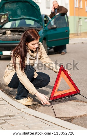 Woman putting triangle sign for car breakdown problem crash warning - stock photo