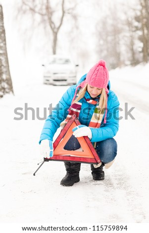 Woman putting warning triangle car breakdown winter snow sign - stock photo