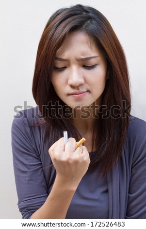woman quits smoking, destroying cigarette on plain blank background