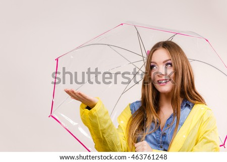 Woman rainy girl in waterproof yellow coat standing with transparent umbrella stretching arm, holds out her palm to catch rain falling water. Forecasting weather season concept