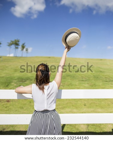 Woman raised up to blue sky and the field , celebrating freedom