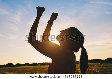 Woman raising arms for celebrating fitness outdoor workout success. Motivation and healthy lifestyle goals concept. - stock photo