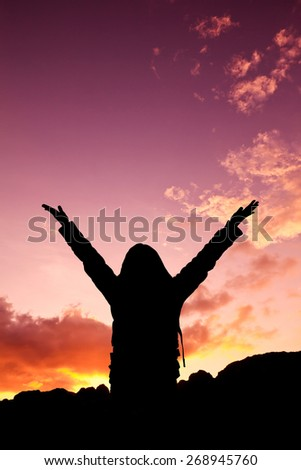 Woman raising her arms on sunset - stock photo
