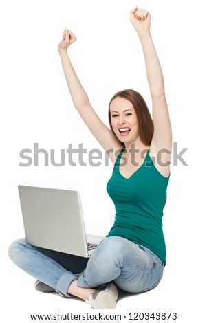 Woman raising her arms while sitting with laptop