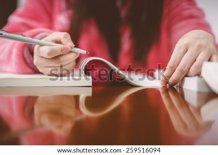 woman read a book and writing. - stock photo