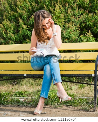 Woman read a magazine in park - stock photo