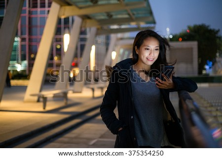 Woman read on text message on phone at night - stock photo