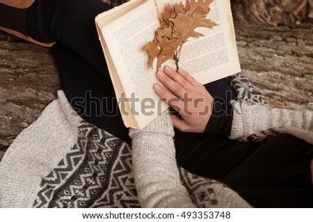 Woman reading a book at the park. Autumn season