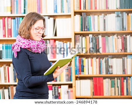 Woman reading a book in front of bookshelves - stock photo