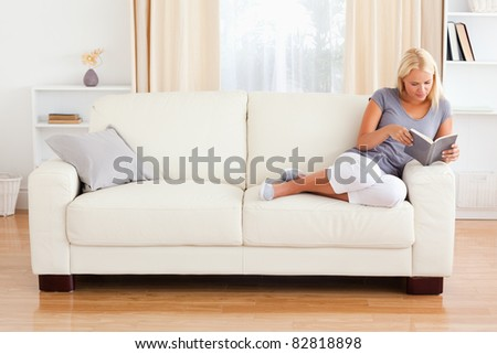 Woman reading a book in her living room - stock photo