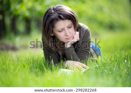 Woman reading a book in the orchard