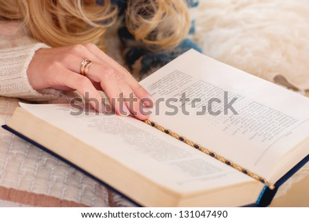 Woman reading a book in the room. Cozy atmosphere. Interesting book. Home to rest. Hand on the page in the book.