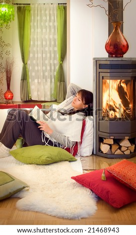 woman reading a book relaxing beside a fireplace. - stock photo