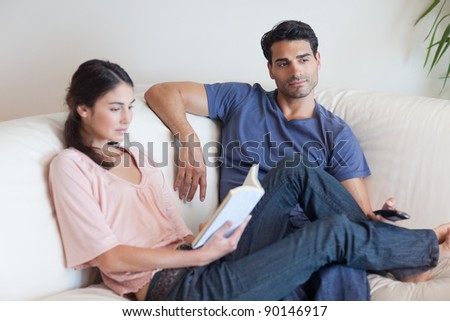 Woman reading a book while her boyfriend is watching television in their living room - stock photo